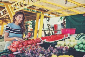 Smiling woman choosing fruits and vegetables on the farmer's market.
